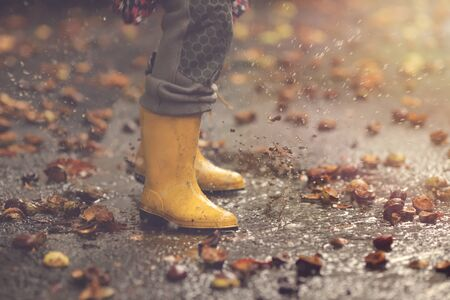 closeup on yellow rubber boots of a child that jumps wildly in a puddle after a rain on an autumn day - childhood and seasonal concept - background blanked out blurry