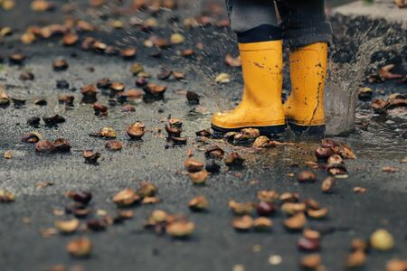closeup on yellow rubber boots of a child that jumps wildly in a puddle on a street after a rain on an autumn day - childhood and seasonal concept - foreground and background blanked out blurry