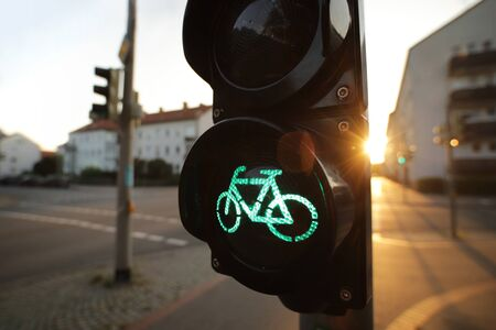 wide angle view on traffic light showing green bicycle symbol at an european intersection in bright morning light - blurred background - urban commuting concept