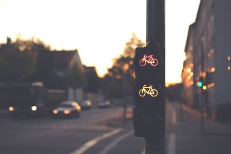 traffic light for a cycling lane showing red and yellow bicycle symbol at an intersection in dark early morning light - blurred background with cars - urban commuting concept