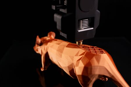 closeup on print head of a 3D-printer manufacturing back of rat sculpture from shiny orange filament in dark surrounding for chinese new year celebration - copy space for text and logo