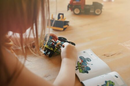 blonde haired young girl puts in a shaft to build a toy tractor from Lego bricks while looking a the assembly instruction - bright light mood with blurred background