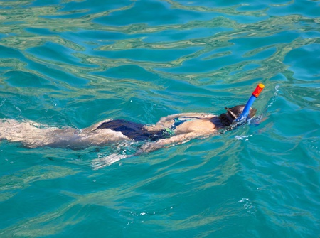 Mladá žena šnorchlování v modré vodě