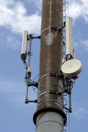 parabola: Modern cell and antenna with flat parabola on blue sky Stock Photo