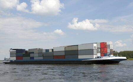 cloudshape: containership on the waal, nearby tiel Stock Photo