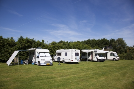 camper: campers on a green grassfield