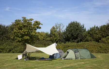 a tent on a camping with blue sky
