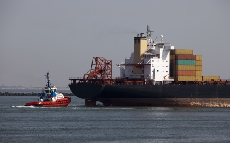 containership: tug with a containership in the harbour of rotterdam
