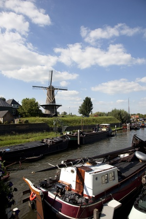dutch windmill with old traditional ship in the front Reklamní fotografie