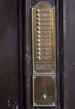 Vintage wall mounted doorbell with beige stone plate, brass buttons, speaker and nameplates Reklamní fotografie - 116086197