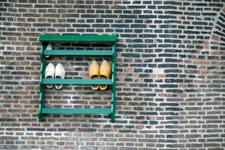 Traditional wooden dutch shoes outside a windmill.