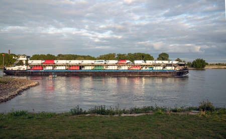 Inlandshipping container vessel transportation containers over the river in the Netherlands Waal River Reklamní fotografie