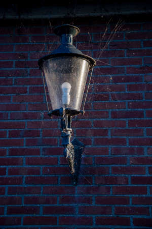 old lamp at night on a dark street with broken glass and full of cobwebs and dust
