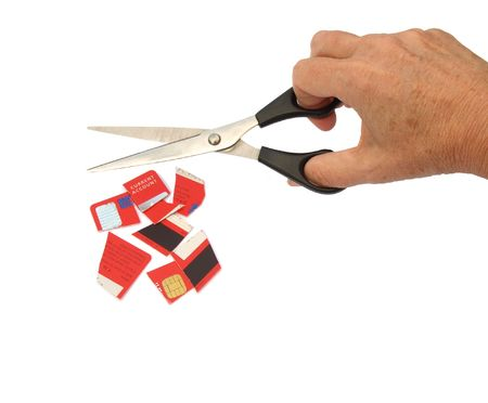 destroying: Hand holding scissors, with a credit card cut into pieces. Isolated on white background.