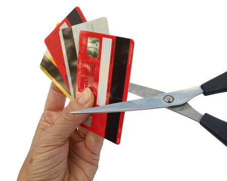 hand cut: Four credit cards held in a hand, being cut up with pair of scissors. Stock Photo