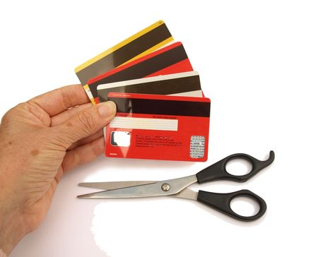 Hand holding four credit card with a pair of scissors nearby. photo