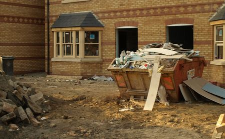 Photograph of a construction site with new houses and skip full of builders rubbish.