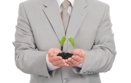 Businessman holding green plant isolated on white