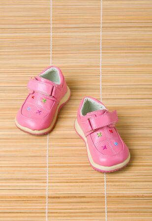 Pink childrens shoes #2 on bamboo background photo