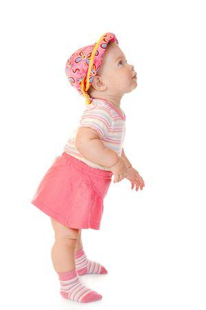 Eerste stappen van de kleine baby in rode jurk geïsoleerd