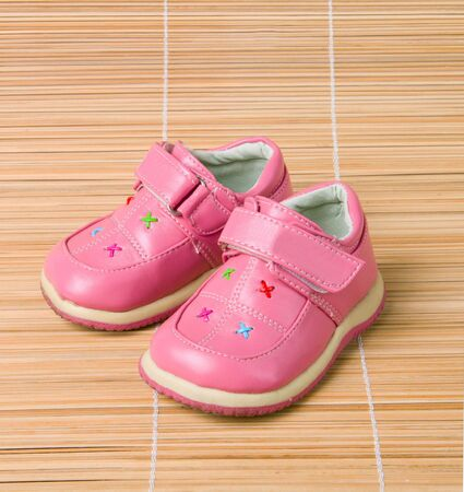 Pink childrens shoes #3 on bamboo background photo