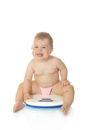 gordo y flaco: Peque�o beb� en casa aislada en las escalas de color blanco  Foto de archivo