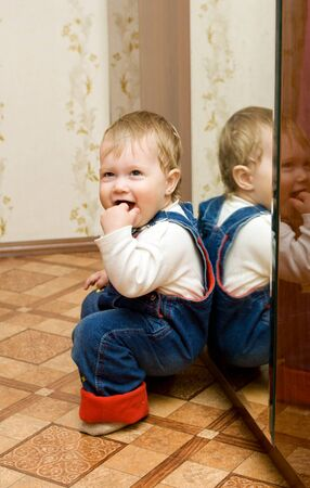 Small smiling baby playing with mirror at home photo