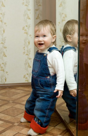 Small smiling baby with mirror at home photo