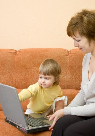 Mother with daughter on sofa with laptop at home Stock Photo - 4321737