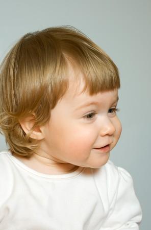 careless: Studio portrait of small smiling girl on grey background Stock Photo