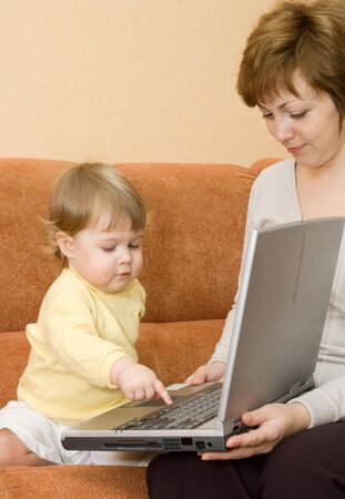 telework: Small girl and mother with laptop at home