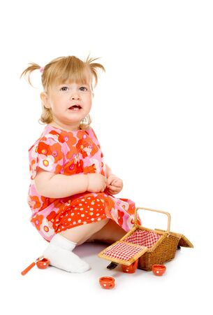 Small smiling baby in red dress with toy basket isolated photo