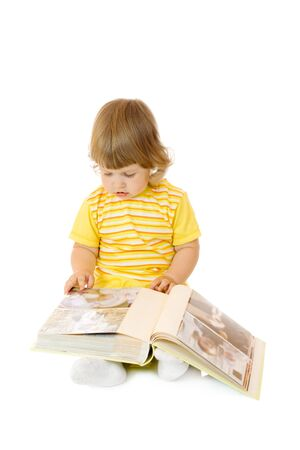 recognized: Small girl browsing an family album (faces on the photos in the album cannot be recognized) Stock Photo