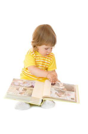 Klein meisje browsen een familie album (gezichten op de foto's kunnen niet worden herkend)