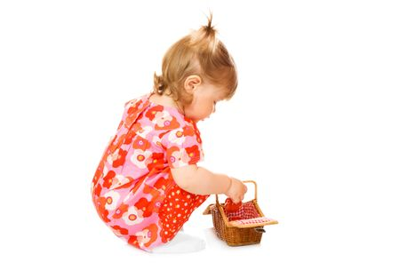 Small in red dress with toy basket isolated photo
