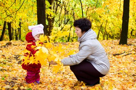 Little girl with her mother on autumn forest photo