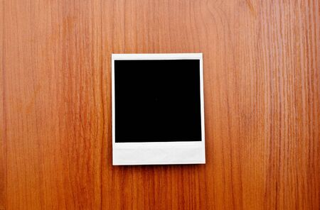 Blank photo frame on wooden board photo