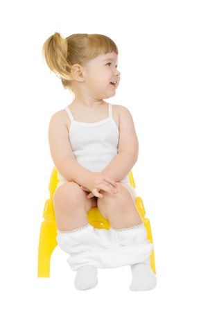 potty: Little curious girl on chamberpot isolated