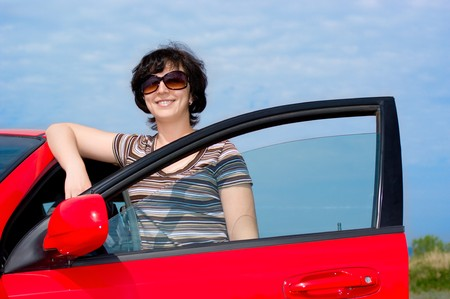 Young smiling woman with red car photo