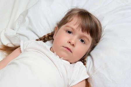 Little sicking girl on pillow photo