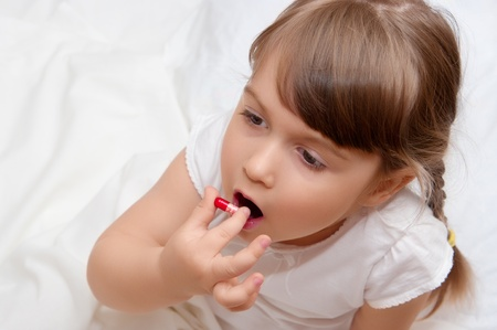 contagious: Little girl with red pill Stock Photo