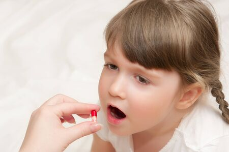 tonsillitis: Woman give red pill to little girl