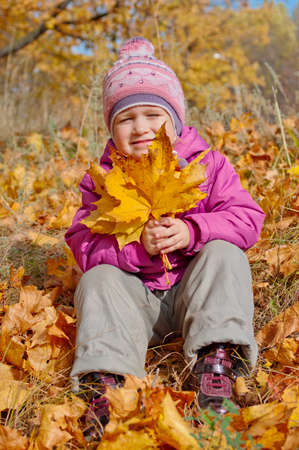 Little girl with yellow leaves in forest photo