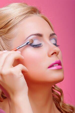 Beautiful young woman applying cosmetic paint brush photo