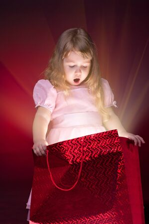 Little girl opening gift packet photo
