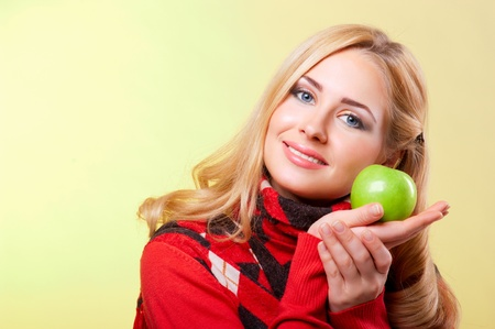 Young woman holding green apple on palm photo