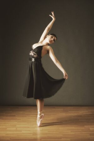 Young dancing ballerina in black costume (ancient style) photo