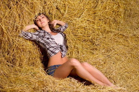 Young woman sitting on haystack photo