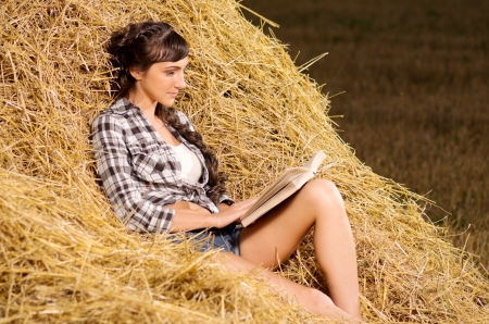 Young woman reading book on haystack photo