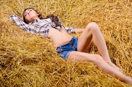 Young girl lying on haystack photo